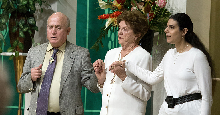 Joe Palona, left, and Francesca Marinaro, far right, pray the Our Father with St. Gabriel parishioner Peggy Keating, center. Palona and Marinaro served as readers at the third annual Mass and reception Nov. 19 for persons with disabilities in Broward County, held at St. Gabriel Parish in Pompano Beach.