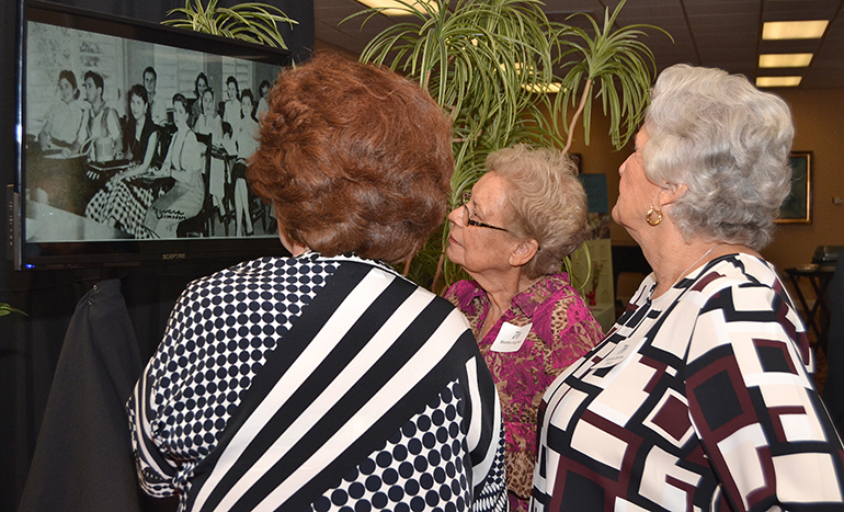Some alumni gather to watch slide shows of historic photos at the 70th anniversary reception for St. Thomas University.
