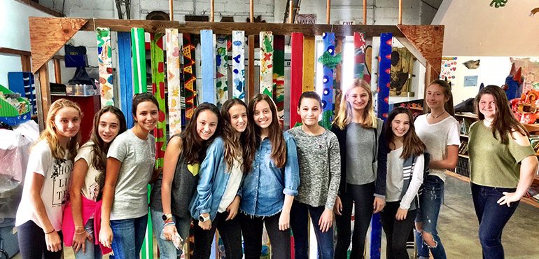 St. Hugh students pose for a photo after their training session at The Barnyard, aimed at helping them gain a more profound outlook on poverty. Pictured are:  Bella Pennekamp, Maria Cardano, Olivia Samur, Isabella Gonzalez, Emiliana Antelo, Alexa Martinez, Helen Lobree, Chelsea Pennekamp, Sofia Rivero, Isabella Camargo, and Solange Aguero.
