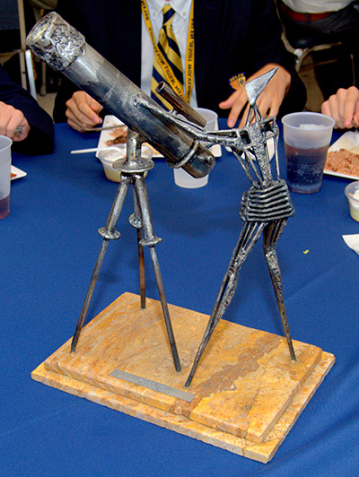 A metal sculpture of an astronomer was among the table centerpieces for a luncheon at the Belen Jesuit Preparatory School during a visit by Brother Guy Joseph Consolmagno, director of the Vatican Observatory. The sculpture was made by Belen alumnus Rafael Consuegra.