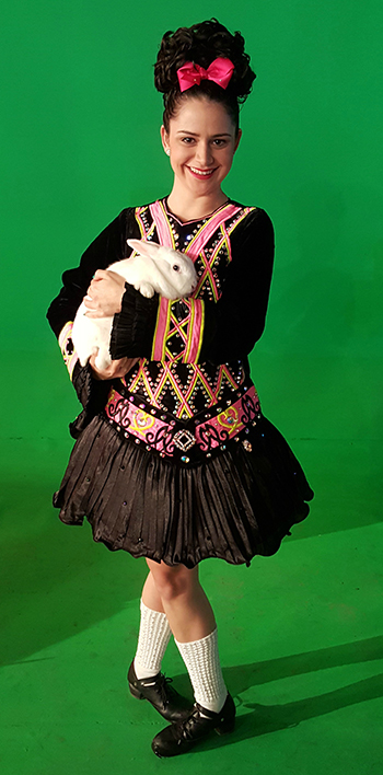 Victoria Molina wearing her Irish step dancing costume: a wig with cascading jet black curls, an elaborately bedazzled dress, and high white socks.