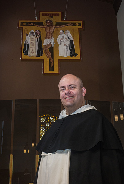 Feb. 2, 2017MARLENE QUARONI | FCDominican Father Cristobal Torres poses in front of the cross he designed for the newly-renovated Cor Jesu Chapel at Barry University.