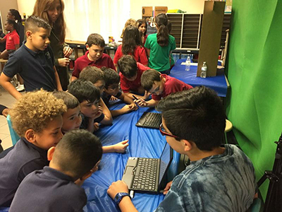 St. Andrew School first-graders learn about the future of cars by listening to middle school students who researched the topic for the Celebrate Engineering Fair.