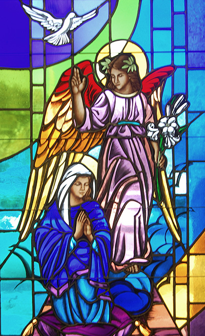 This stained glass window at St. Maximilian Kolbe Church in Pembroke Pines depicts the angel Gabriel announcing to a humble Mary that she will bear the Son of God. He holds Easter lilies, a symbol of the death and resurrection of Jesus. A hovering dove symbolizes the Holy Spirit.