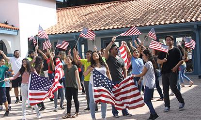 """Durante la grabación del video oficial del V Encuentro """"Nuestra Alegría"""", los jóvenes de diferentes grupos de la Pastoral Juvenil Hispana de Miami que participaron bailan con las banderas de Estados Unidos, para mostrar la unidad en la diversidad, uno de los mensajes que quiere promover el video."""