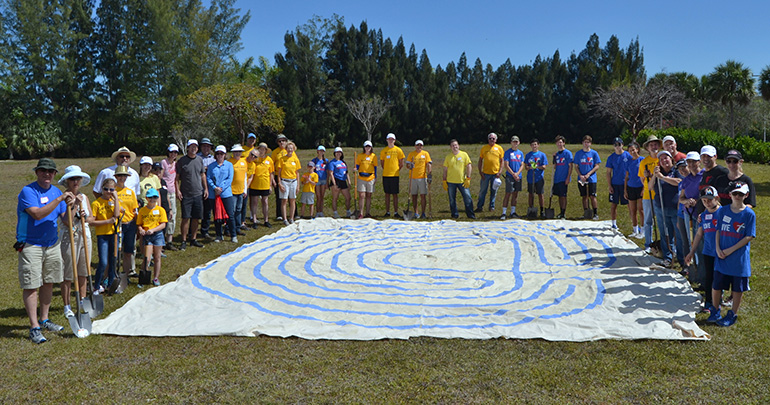 Workers line a cloth labyrinth, showing the size of the structure for which they broke ground.