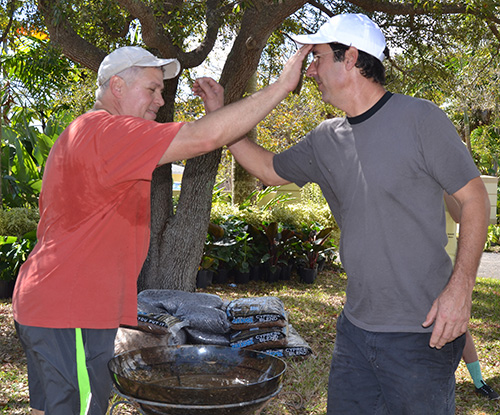 Michael DeFerrari, left, and Tony Buzone bless each other during groundbreaking for the new Prayer Labyrinth.