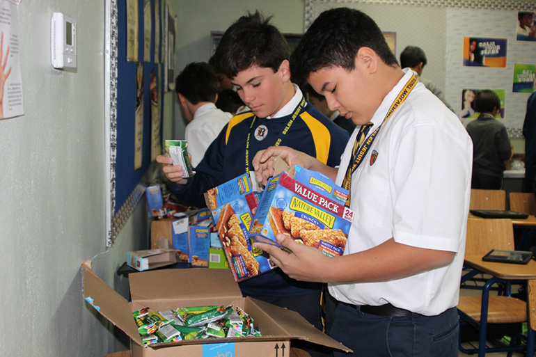 Belen Jesuit Prep's seventh graders assemble care packages for the homeless during the culmination of Ignatian Week March 17.