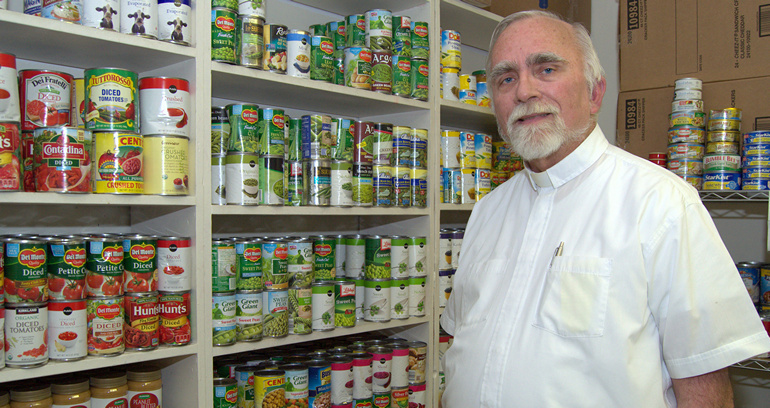 Father Stephen Hilley of St. Justin Martyr shows some of the foods he stocks for the poor on Key Largo.