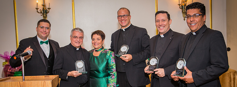 Current and former staff of St. Michael are recognized during the 65th anniversary gala for St. Michael School. From left: Alfonso Balmaceda, religious education coordinator; Father Gerardo Diaz, pastor; Carmen Alfonso, principal; Father Christopher Marino, prior pastor and currently rector of St. Mary Cathedral; Father Richard Vigoa and Father Giovanni Peña, both former parochial vicars. Father Peña is now administrator of Prince of Peace Church in Miami and Father Vigoa is secretary to Archbishop Thomas Wenski.