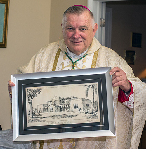 Archbishop Thomas Wenski holds a drawing of the original architectural sketch for St. Anthony School which principal Tery Maus presented to him.