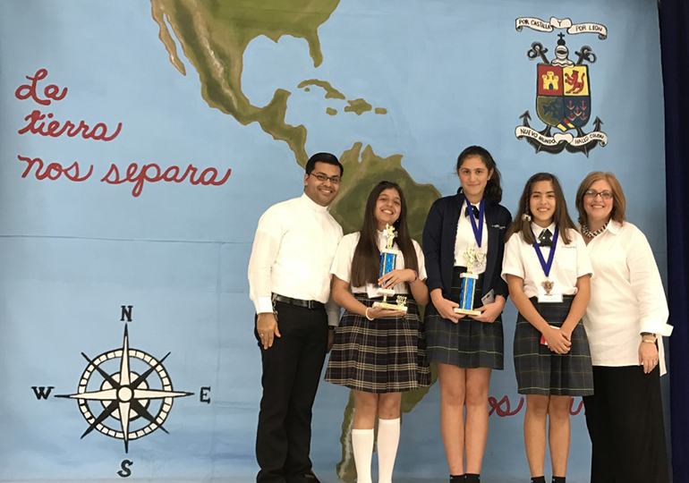 Father Yamil Miranda, parochial vicar at Blessed Trinity, and school principal Maria Teresa Perez pose with the Spanish Spelling Bee winners, from left: Andrea Schroeder, St. Andrew School, first place; and second and third place winners Camila Suels and Ana Serratos, both of St. Thomas the Apostle School in Miami.