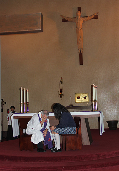 Father Gerardo Diaz, St. Michael's pastor, hears the confession of a St. Michael student.