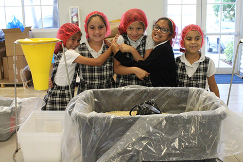 Hold on, things are about to get messy: Third graders from Our Lady of Lourdes prepare for food packing instructions.