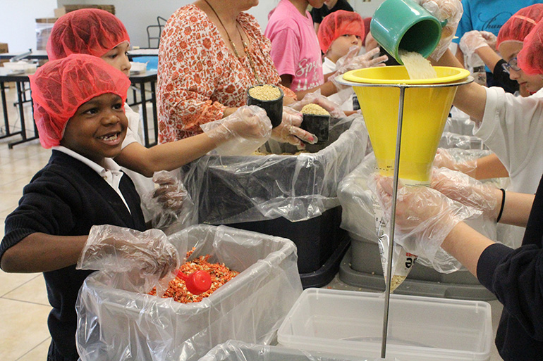 A second grader smiles as he prepares to pour in dried vegetables to the meal bag mix.