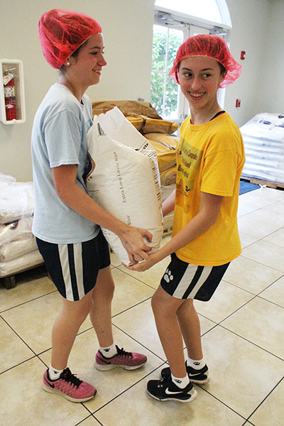 Our Lady of Lourdes students Lauren Cuellar and Nicole Alpizar carry a bag of rice to a meal packing station in need of a refill.