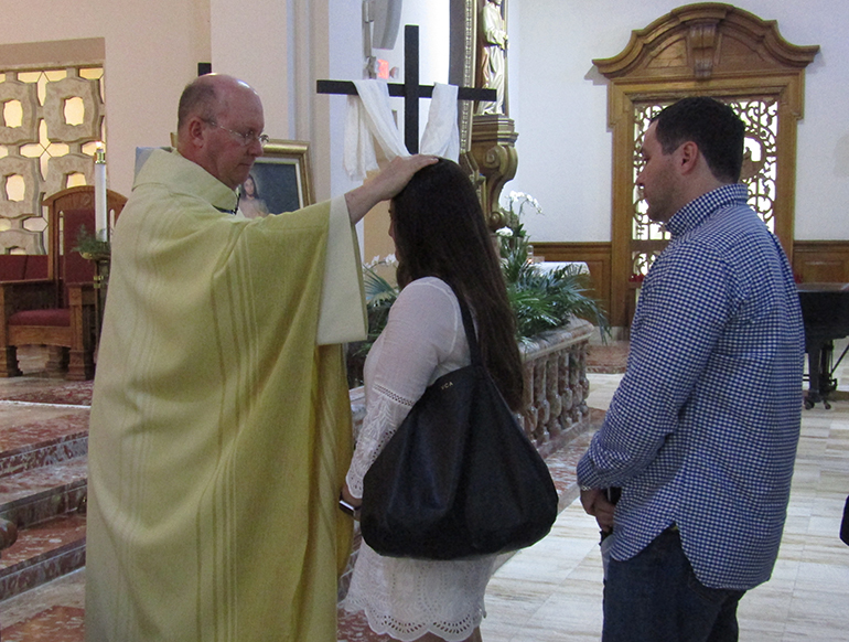 Father Michael Davis, Little Flower's pastor, anoints Vanessa and Alex Arvesu after the second annual Infertility Mass at the parish April 23. The start of National Infertility Awareness Week this year coincided with the second Sunday of Easter, feast of Divine Mercy.