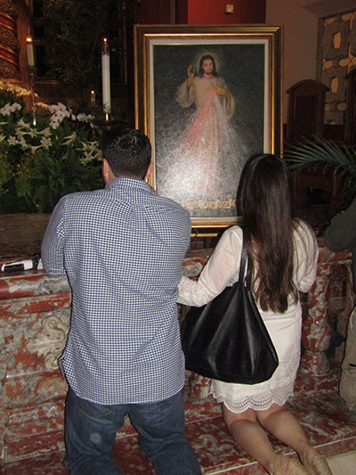 Vanessa and Alex Arvesu pray in front of an image of Divine Mercy after the second annual Infertility Mass at Little Flower Parish, Coral Gables, April 23. The start of National Infertility Awareness Week this year coincided with the second Sunday of Easter, feast of Divine Mercy.