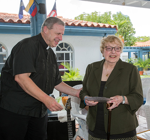 Msgr. Pablo Navarro presents Zoila Diaz, the second director of the Lay Ministry Office, with a token of recognition for her years of service.