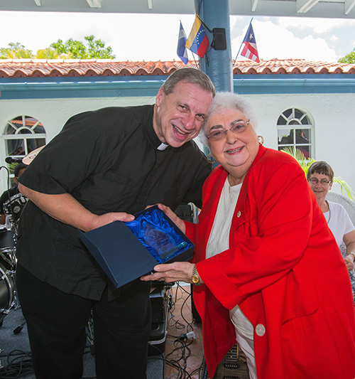 Msgr. Pablo Navarro poses for a photo with Leyla Mazpule, who received a glass flame for being the longest serving lay minister. She is from the original School of Ministry class that graduated in 1979.