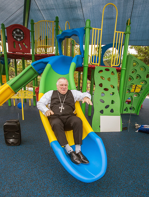 Archbishop Thomas Wenski tries out one of the slides on the play structure of the Sister Lucia Sport and Fitness Park at the Marian Center.