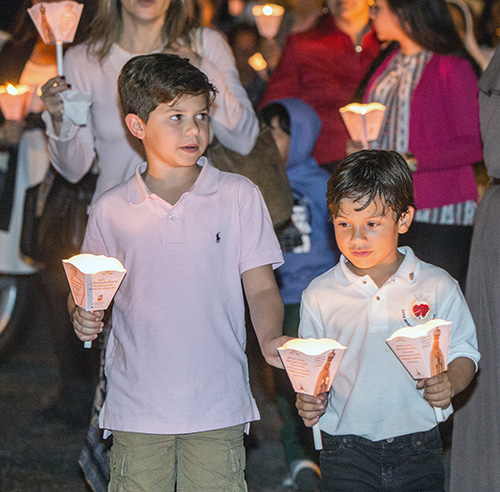 Max Gabaldon, 8, and Gabriel Echevarria, 6, carry candles in the procession around the grounds of St. Michael the Archangel Church in Miami.