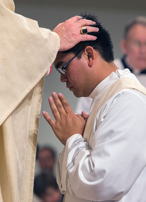 By the laying on of hands, Archbishop Thomas Wenski ordains Father James Arriola.
