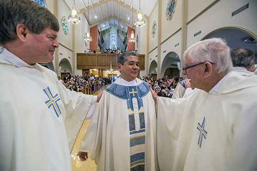Father Steven O'Hala, left, and Msgr. Seamus Doyle, right, help newly-ordained Father Edgardo