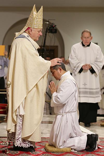 Archbishop Thomas Wenski lays hands on Edgardo