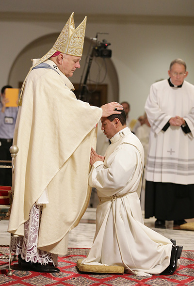 Archbishop Thomas Wenski lays hands on Luis Flores, ordaining him to the archdiocesan priesthood.