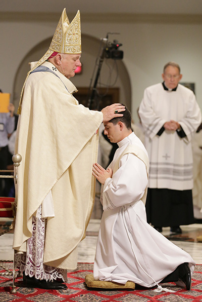 Archbishop Thomas Wenski lays hands on Alexander Rivera, ordaining him to the archdiocesan priesthood.
