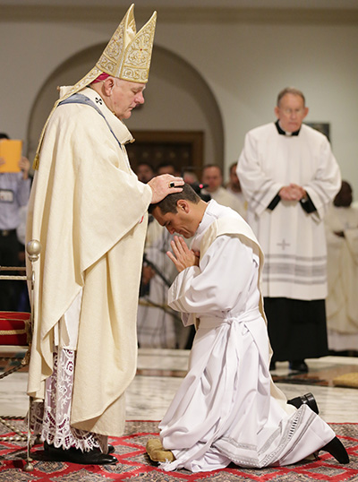 Archbishop Thomas Wenski lays hands on Juan Carlos Salazar, ordaining him to the archdiocesan priesthood.