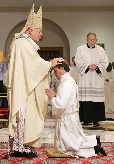 Archbishop Thomas Wenski lays hands on Oswaldo Agudelo, ordaining him to the archdiocesan priesthood.
