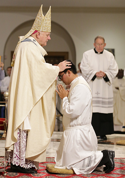 Archbishop Thomas Wenski lays hands on James Arriola, ordaining him to the archdiocesan priesthood.