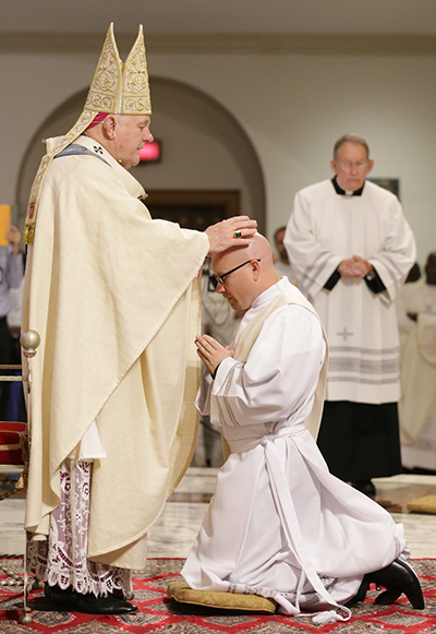 Archbishop Thomas Wenski lays hands on Luis Pavon, ordaining him to the archdiocesan priesthood.
