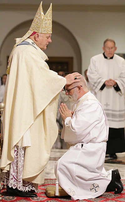 Archbishop Thomas Wenski lays hands on Joseph Maalouf, ordaining him to the archdiocesan priesthood.