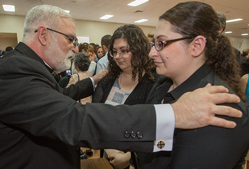 Newly ordained Father Joseph Maalouf blesses his daughters, Mary Maalouf, left, and Angie Maalouf, after the Mass.
