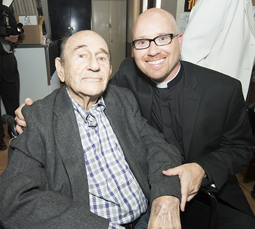 Newly ordained Father Luis Pavon poses with his namesake and grandfather, Luis Rodriguez Iznaga, who was celebrating his 98th birthday the day of his grandson's ordination. The elder Luis had considered the priesthood when he was young, but said life circumstances at the time interfered. Now his grandson will fulfill that dream.