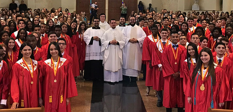 Msgr. Edward Pace High School's Class of 2017 pose for a photo after their baccalaureate Mass with, from left: altar server Alex Gomez (Class of 2011); Pace President Father Paul Vuturo; Father Bryan Garcia (Class of 2006); altar server Mark Gomez (Class of 2013); and Deacon Matthew Gomez (Class of 2009).