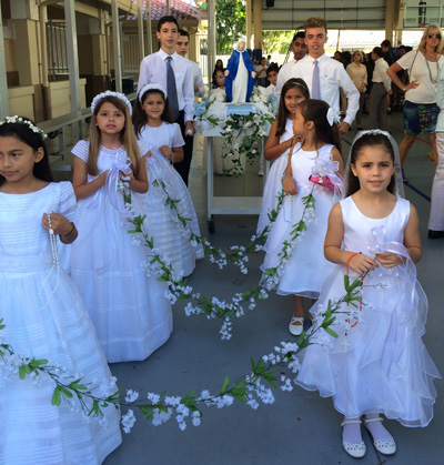 Second graders from St. Bonaventure School, wearing their first Communion dresses and carrying garlands of flowers, lead the procession in honor of Mary.