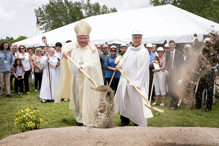 Miami Auxiliary Bishop Peter Baldacchino, left, and Father Thomas Wisniewski, who was pastor until his retirement June 1, break ground May 24 for a new Mary Help of Christians Catholic School Parish & Student Center.