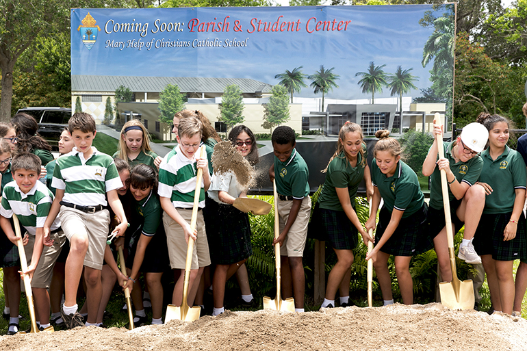 Students lend a hand at the May 24 groundbreaking for a new Mary Help of Christians Catholic School Parish & Student Center. The $ 3.2 million, 15,000-feet structure will allow students to eat lunch inside as well as provide additional space for administrative offices and classrooms.