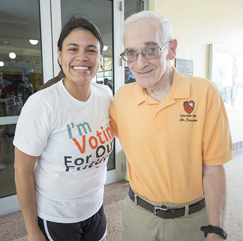 Lucia Baez, a 2001 Archbishop Curley-Notre Dame graduate, poses with her former English teacher, and the school's cross-country coach, Christian Brother John Corcoran.