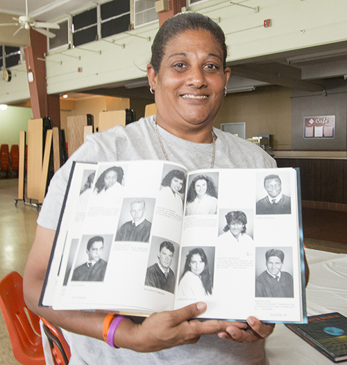 Frances Fresneda, a 1989 graduate of Archbishop Curley Notre Dame High School, poses with her yearbook picture. She now teaches physical education at St. James School in North Miami.