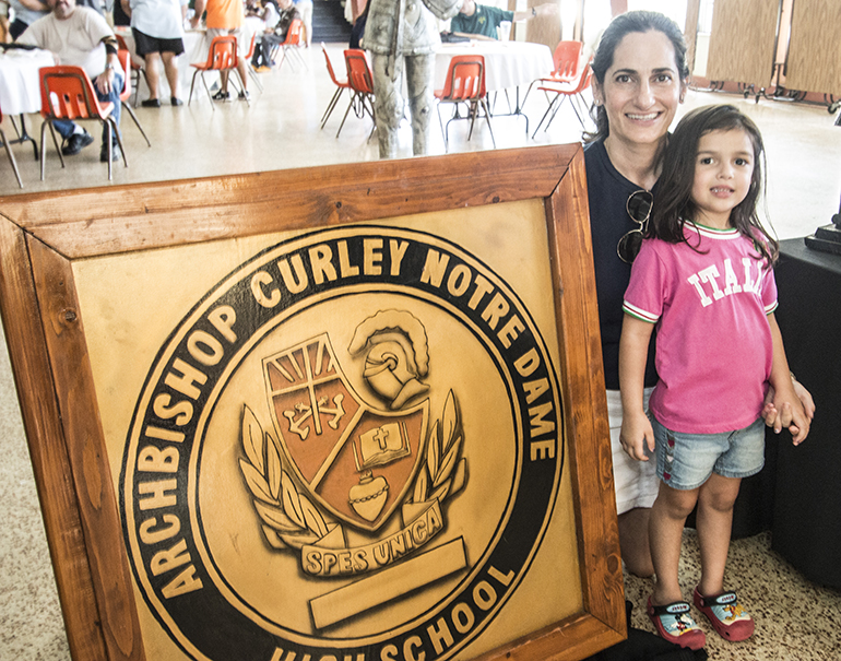 Selena Samios Smith, a 1990 graduate, poses with the Archbishop Curley-Notre Dame seal and her daughter, Marya Smith.