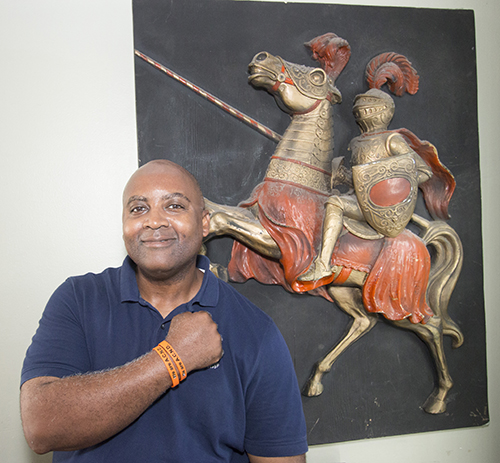 Vonley Williams, Archbishop Curley-Notre Dame class of 1986 and now a resident of Plantation, poses in front of a relief of the school mascot, a Knight. The orange bracelet says,