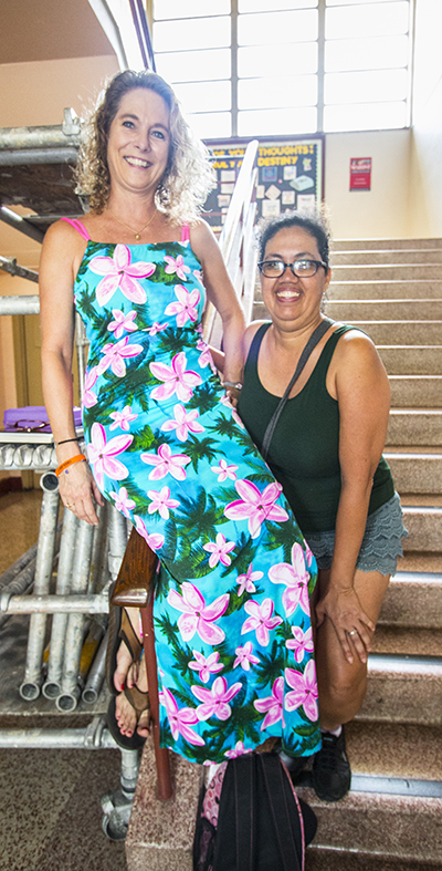 Kristine-Marie Lachance, left, class of 1986, slides down the banister just as she did when she was a student at Archbishop Curley-Notre Dame High School. At right is her