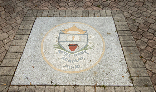 Shield of Notre Dame Academy, the all-girls school which merged with Archbishop Curley in 1981. Both schools were founded in 1953 and were the first to be integrated in Florida, in 1960. Notre Dame alumni have successfully petitioned to have it moved from its current site at Curley-Notre Dame to its original site at what is now Notre Dame d'Haiti Mission in Miami.