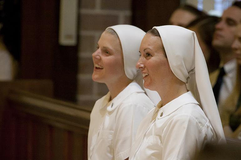 La Hna. Molly Joyce del Corazón Misericordioso de Jesús, a la izquierda, y la Hna. Monica Bernadette de la Inmaculada Concepción sonríen durante el comienzo de la Misa celebrando su profesión de primeros votos. La Misa tuvo lugar en la iglesia St. Raymond, en Miami.