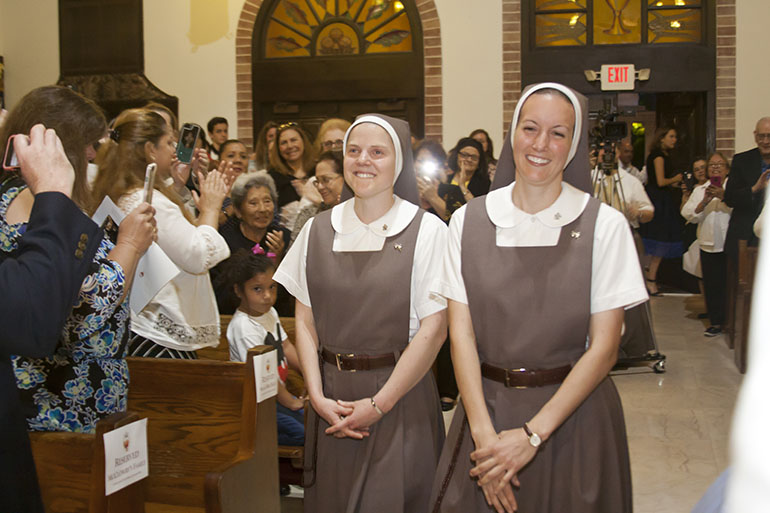 Sister Molly Joyce of the Merciful Heart of Jesus, left, and Sister Monica Bernadette of the Immaculate Conception enter St. Raymond Catholic Church after receiving their full habit and veil.